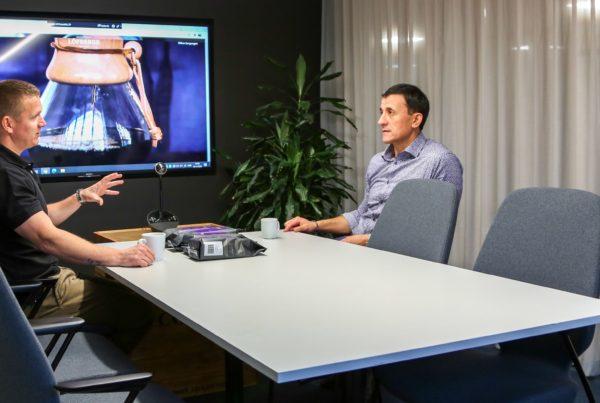 To menn diskuterer fairtrade kaffe på møterom