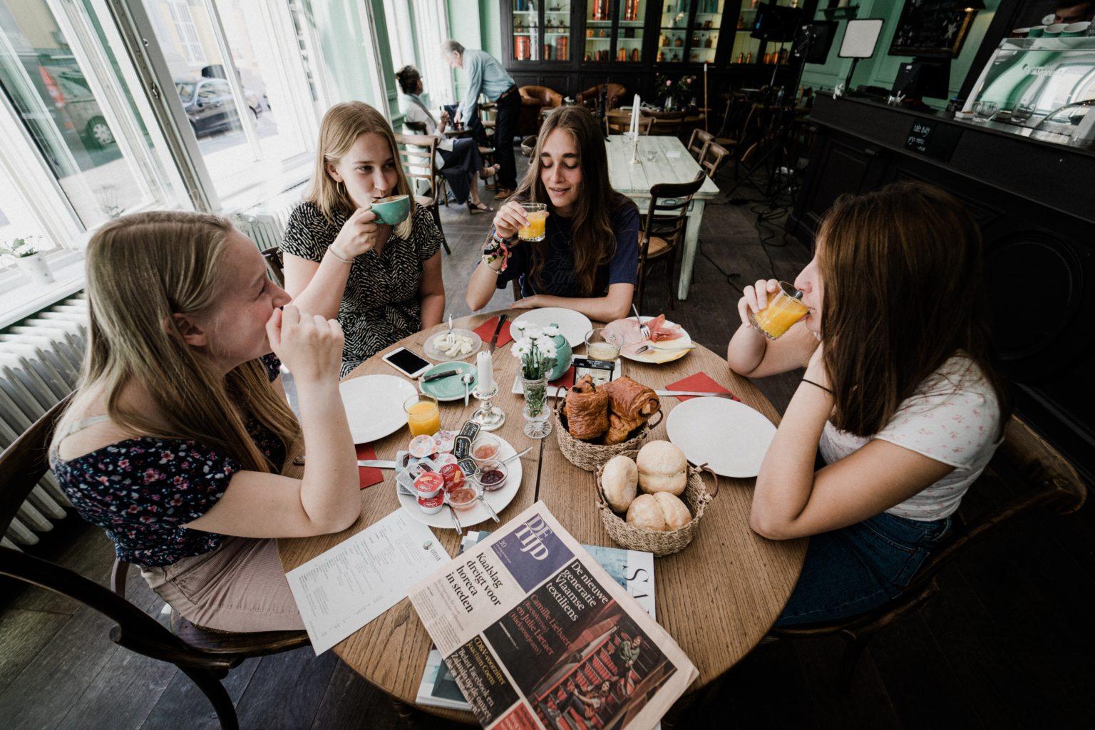 damer drikker kaffe rundt bord