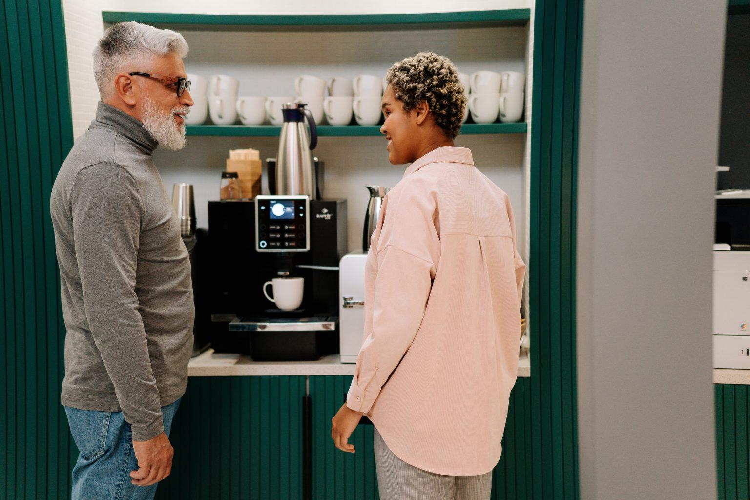 to personer ved kaffemaskin